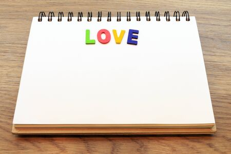 lay down: wood colorful letter word love lay down notebook on wood background concept