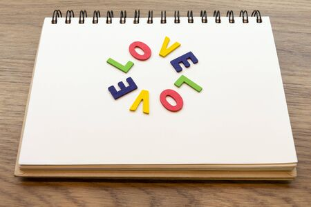 lay down: Wood colorful letter word love lay down notebook on wood desk concept. Stock Photo