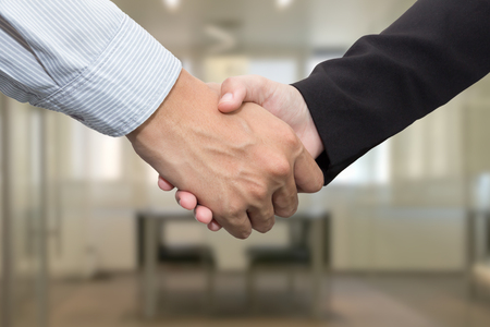 people shaking hands: Close up of businessmen shaking hands in meeting room Stock Photo