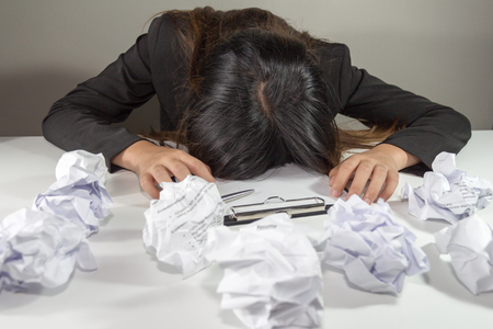Stressed business woman make a mistake with chewed paper - night overtime work. Stock Photo