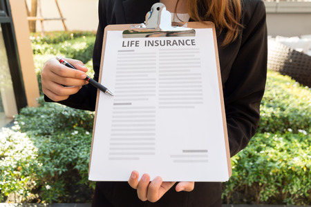 life insurance: Women in suit showing life insurance policy and pointing with a pencil