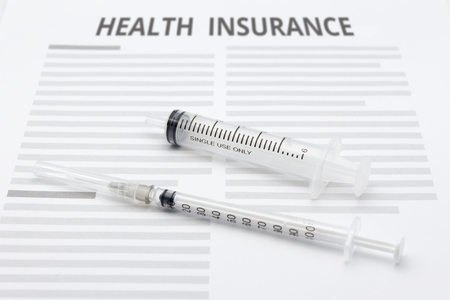 hypodermic syringe: Health insurance form with hypodermic syringe