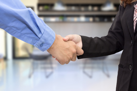 people shaking hands: Close up of businessmen shaking hands in meeting room.