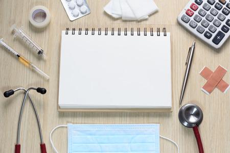 estetoscopio: Vista superior de escritorio de los doctores con el estetoscopio, jeringa hipod�rmica, yeso, gasas, medicamentos, calculadora, masque, cinta y calculadora.