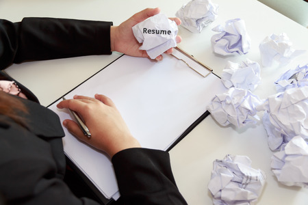 crumple: Hands of female crumple sheets of Resume at the desk, mistake resume. Stock Photo