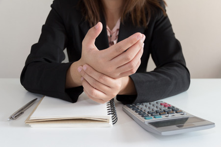 finger on trigger: Businesswoman get pain hand while working in his office. Stock Photo
