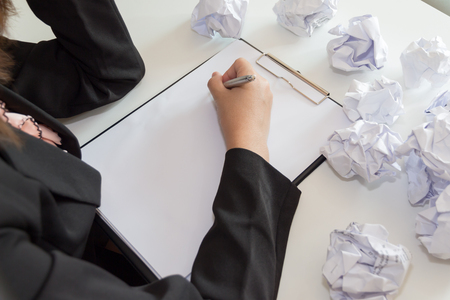 crumple: Hands of female writing with crumple paper at the desk.