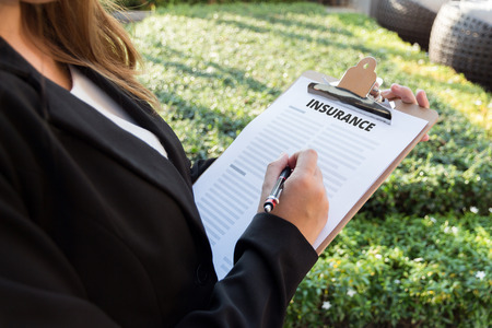 insurer: Businesswoman signing a insurance policy on the street. Stock Photo