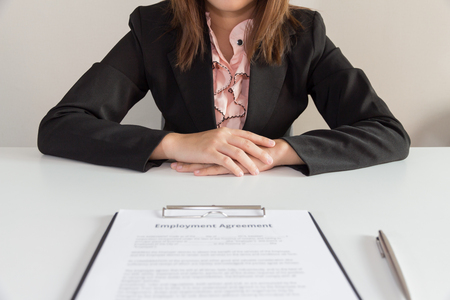 puesto de trabajo: Empresaria que se sienta con el contrato de trabajo delante de ella. Foto de archivo