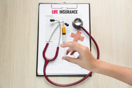 health insurance: Hand holding syringe, Life insurance form with stethoscope Stock Photo