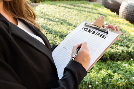 commercial law: Businesswoman signing insurance policy in the garden.