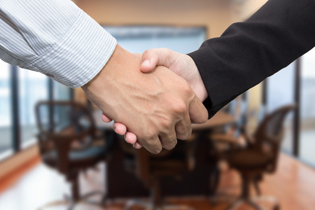 female hand: Close up of businessmen shaking hands in meeting room.
