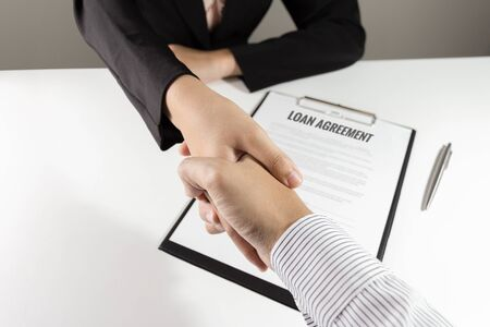 lend a hand: Businessman and businesswoman handshake over loan agreement document.