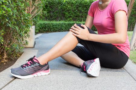 女性ランナーに触れる彼女の膝の怪我 写真素材