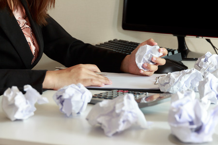 crumple: Hands of female crumple sheets of papers at the office desk.