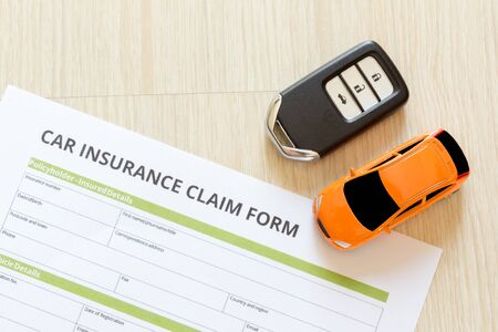 reimbursement: Top view of car insurance claim form with car key and car toy on wooden desk
