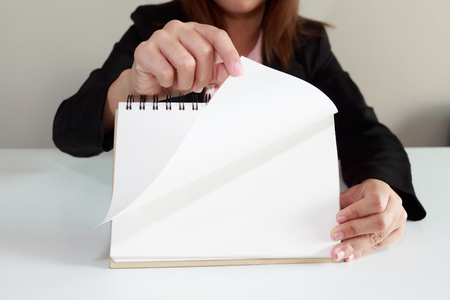 turning page: Businesswoman hand turning page of notebook concept