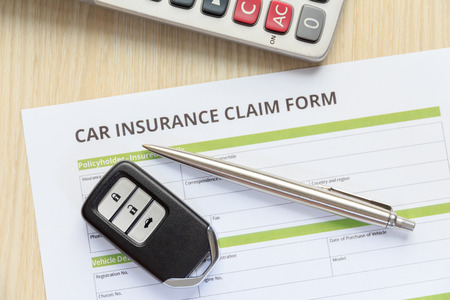 reimbursement: Top view of car insurance claim form with car key and pen on wooden desk concept