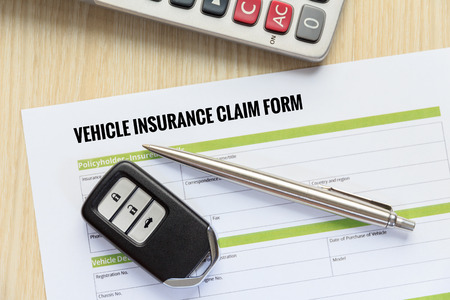 reimbursement: Vehicle insurance claim form concept with car key and calculator lay down on wooden desk.