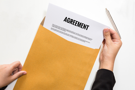 concur: Businesswoman opening agreement document in envelope.