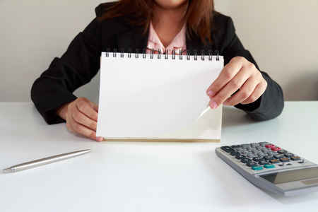 turning page: Businesswoman hand turning page of notebook.
