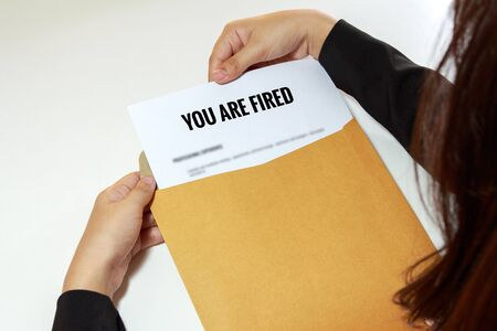 terminated: Businesswoman opening the Fired document in letter envelope. Stock Photo