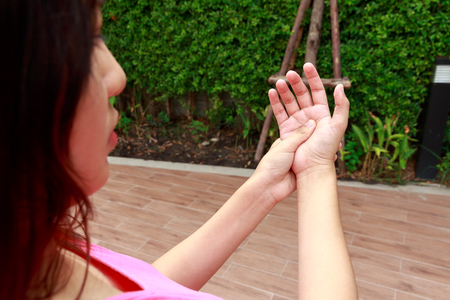 stiffness: Woman hands pain in garden concept