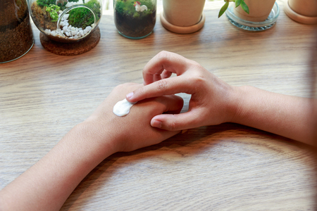 moisturiser: Young woman applying hands cream on wooden table.