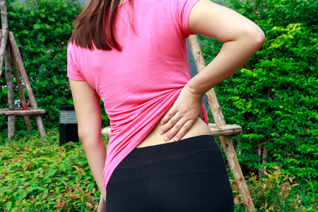 Female athlete lower back painful injury. Sporty woman backache and injury concept Zdjęcie Seryjne