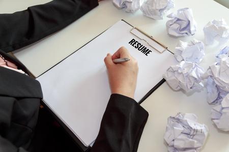 여성의 사무실 책상에서 서류의 crumple 시트와 함께 이력서 작성의 손.