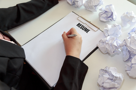 mistakes: Hands of female writing resume with crumple sheets of papers at the office desk.