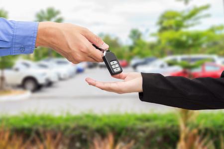 lend a hand: Businesswomen giving a key car to businessman at car parking.