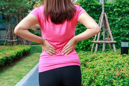 back ache: Female athlete lower back painful injury. Sporty woman backache and injury.