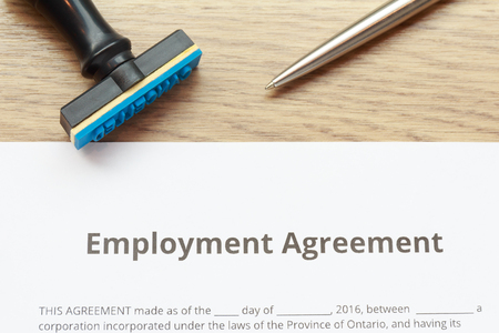 Employment Agreement document lay down on wooden desk with rubber stamp and pen. Zdjęcie Seryjne