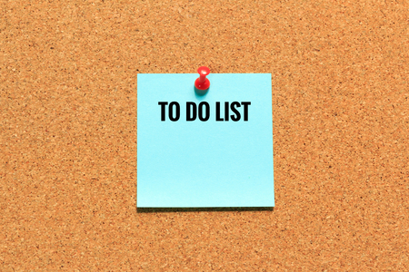 red pin: Blue sticky note on cork board with push red pin.