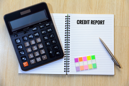 bank records: Credit report on notepad with calculator, colorful bookmark and pen.