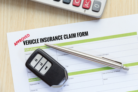 reimbursement: Top view of Approved vehicle insurance claim form with car key, pen and calculator on wooden desk concept Stock Photo