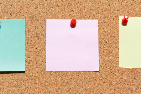 push in pins: Cork board with colorful blank notes and push pins. Stock Photo
