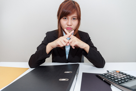 impede: Businesswoman says no with cross fingers on at her office.