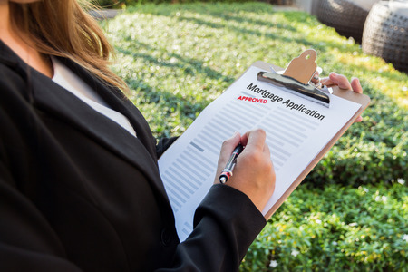 mortgage application: Businesswoman signing approved mortgage application in the garden. Stock Photo