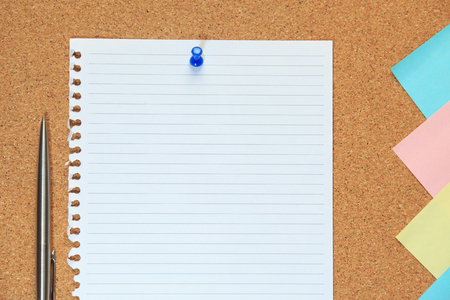 cork sheet: Cork board with sheet of paper, colorful blank notes and push pins.