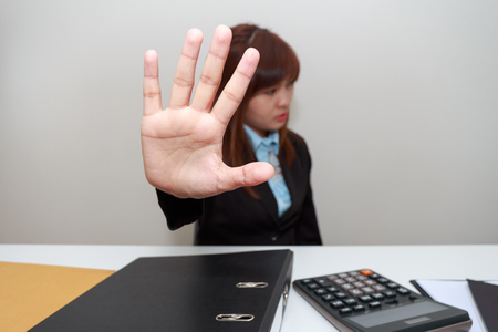 impede: Businesswoman says no or hold on at her office. Stock Photo