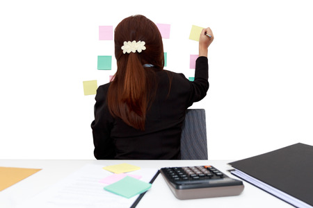 labyrinthine: Businesswoman writing on sticky note on the wall behind her - white background concept Stock Photo