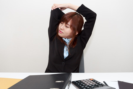 Businesswoman stretching herself or exercise while working at office