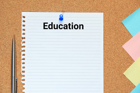 cork sheet: Education wording on cork board with sheet of paper, colorful blank notes and push pins.