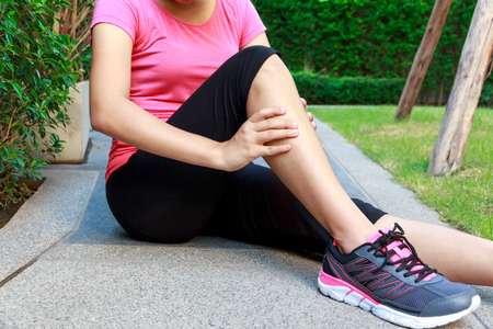 stiff: Asian sporty woman leg pain or calf muscle while jogging or running.