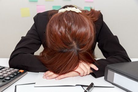overwork: Stressed businesswoman bend down the head or sleep at her desk, overwork concept Stock Photo