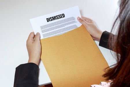 dismissed: Businesswoman hands holding the dismissed document in envelope. Stock Photo