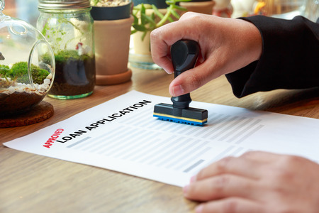 lend a hand: Hands holding rubber stamp with approved loan application on wooden desk.
