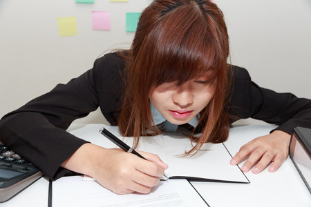 somnolent: Sleepy and tired business woman at desk, holding a pen for writing and close her eyes - business concept Stock Photo